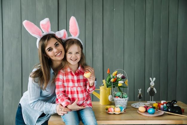 Mujer joven abrazando a hija en orejas de conejo Foto gratis