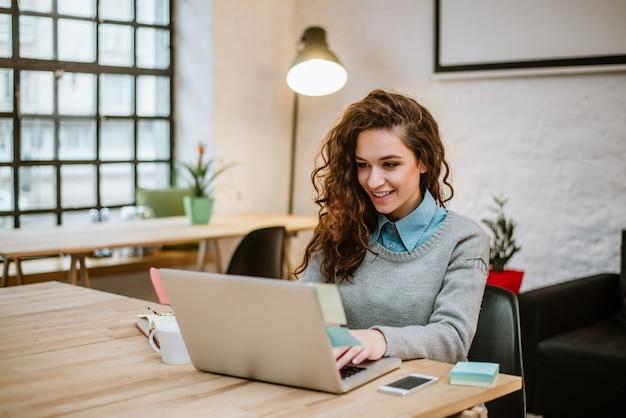 Mujer joven acertada en la oficina moderna que trabaja en la computadora portátil. Foto Premium