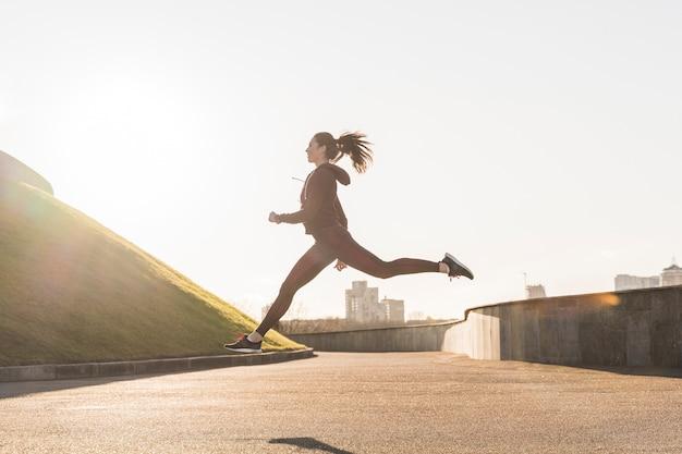 Mujer joven activa corriendo al aire libre Foto gratis