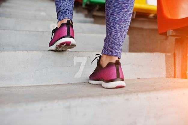 Mujer joven activa corriendo en las escaleras en el estadio. Foto Premium