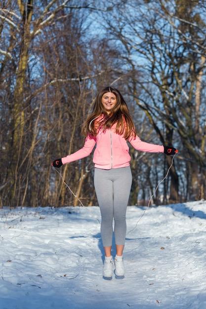 Mujer joven activa realiza un ejercicio con una cuerda de saltar Foto Premium