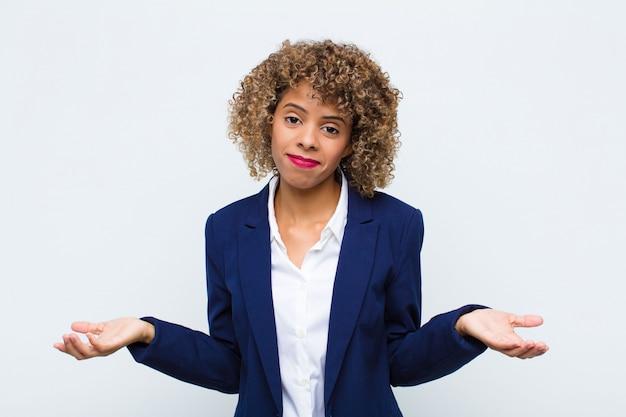 Mujer joven afroamericana sintiéndose desorientada y confundida, sin saber qué opción u opción elegir, preguntándose contra la pared plana Foto Premium