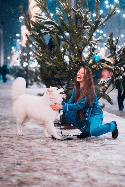 Mujer joven agachada junto a un perro en una calle de invierno Foto gratis
