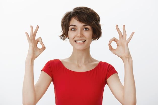 Mujer joven alegre garantiza una calidad perfecta, recomienda el producto, mostrando un gesto bien Foto gratis