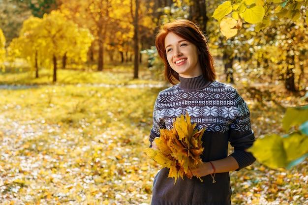 Mujer joven alegre en el parque del otoño que sonríe en un día soleado. Foto Premium