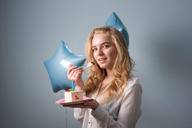 Mujer joven alegre con pastel de cumpleaños Foto gratis