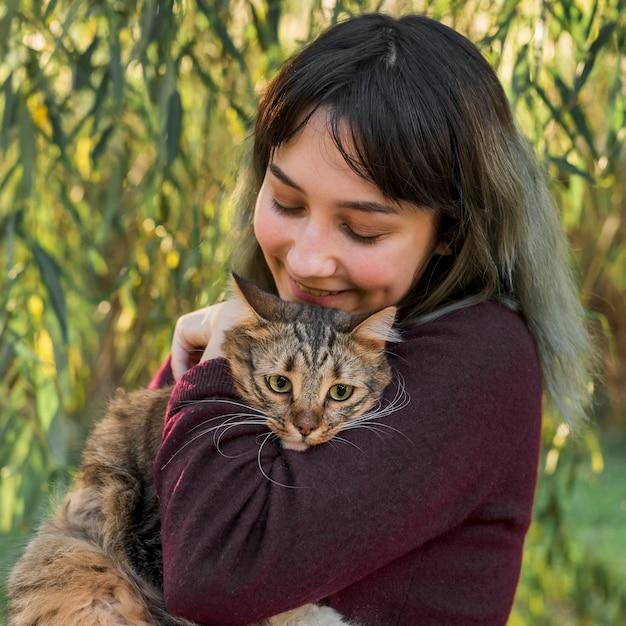 Mujer joven alegre que ama su gato atigrado en jardín Foto gratis