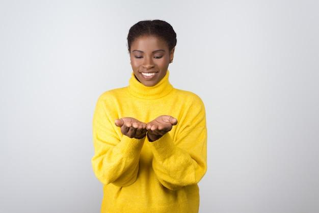 Mujer joven alegre que muestra las palmas Foto gratis
