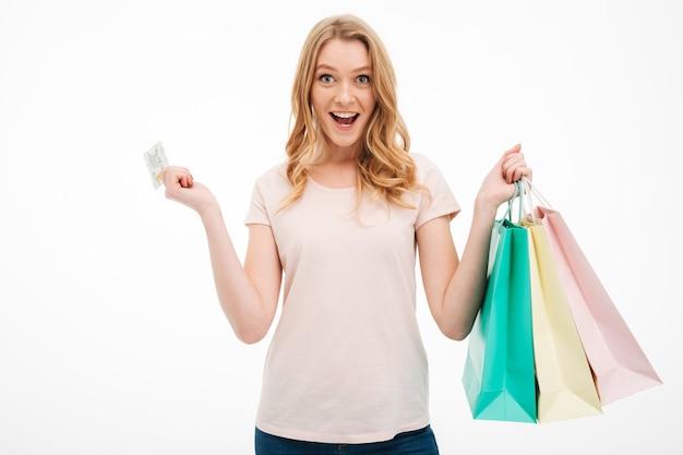Mujer joven alegre que sostiene la tarjeta de crédito y bolsos de compras. Foto gratis