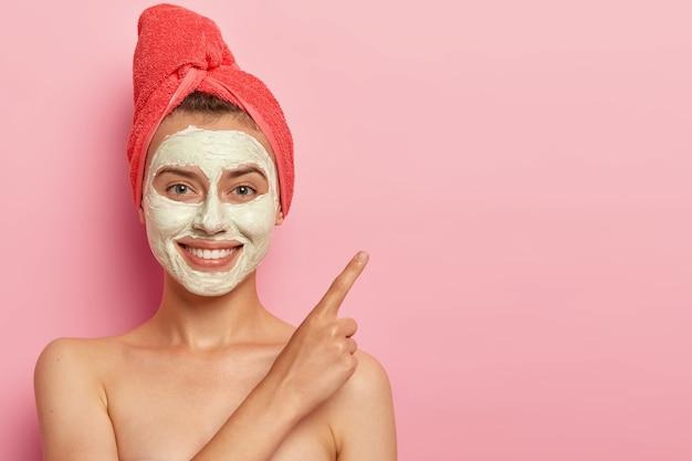 Mujer joven alegre con suave sonrisa, señala el dedo índice Foto gratis