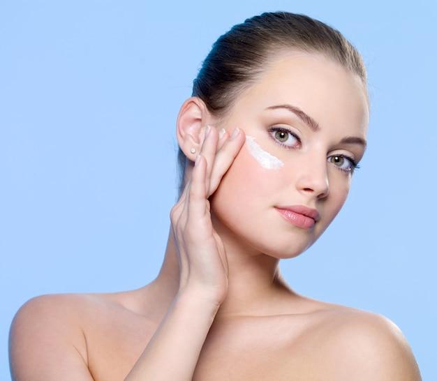 Mujer joven aplicar crema en el rostro en azul Foto gratis