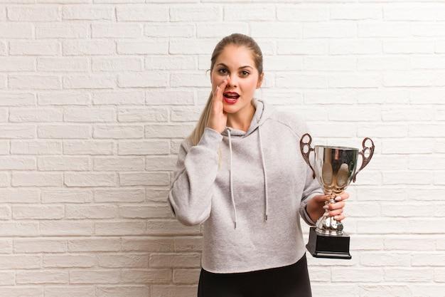Mujer joven de la aptitud rusa que sostiene un trofeo Foto Premium