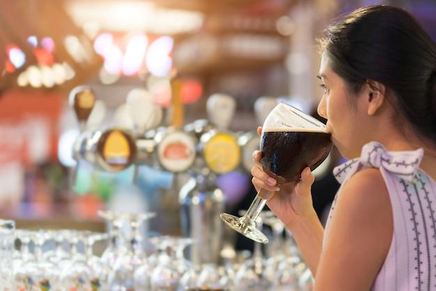 Mujer joven de asia que bebe la cerveza negra mientras que fija en la barra contraria. Foto Premium