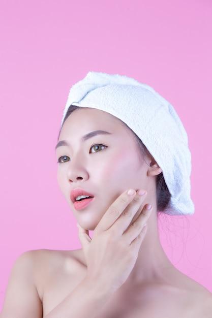 Mujer joven de asia con rostro limpio y fresco, toque en la cara, expresiones faciales expresivas, cosmetología y spa. Foto gratis