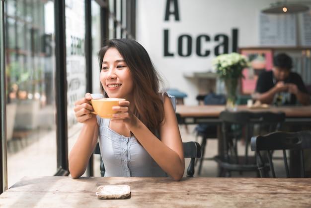 Mujer joven asiática alegre que bebe el café o el té caliente que lo goza mientras que se sienta en café Foto gratis