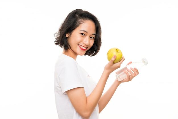 Mujer joven asiática con una manzana y una botella de agua Foto Premium