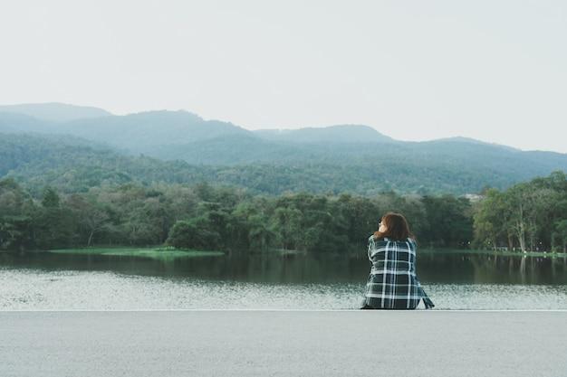 Mujer joven asiática de pie frente al mar Foto Premium
