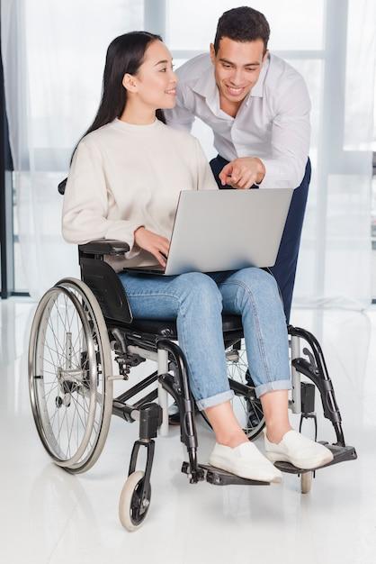 Mujer joven asiática que se sienta en la silla de rueda que mira al hombre que muestra algo en el ordenador portátil Foto gratis