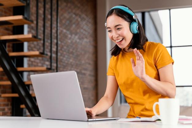 Mujer joven asistiendo a clases online Foto gratis