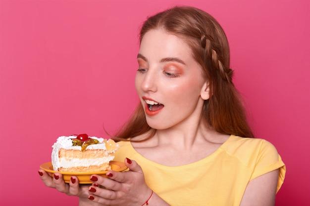 Mujer joven atractiva con la boca abierta tiene placa con pedazo de delicioso pastel en las manos. señora de cabello castaño con manicura roja Foto gratis