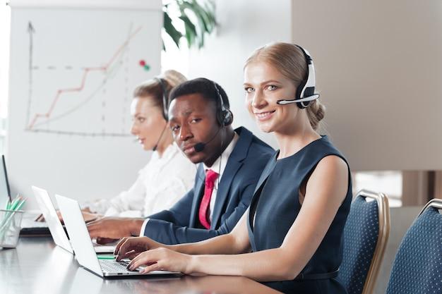 Mujer joven atractiva que trabaja en un centro de llamadas con sus colegas Foto Premium