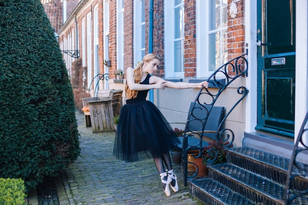Mujer joven bailarina con el pelo rojo en traje de ballet y zapatillas de punta está en pose hermosa bailando en la calle. Foto Premium