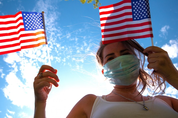 Mujer joven con bandera estadounidense en el cielo azul con luz solar y máscara de seguridad para covid-19 saludando a estados unidos Foto Premium