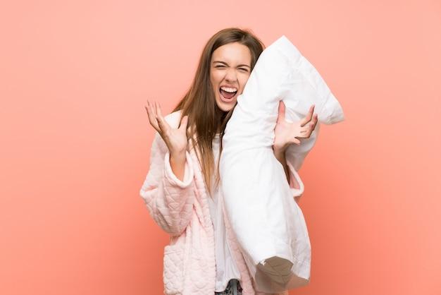 Mujer joven en bata sobre pared rosa infeliz y frustrada con algo Foto Premium