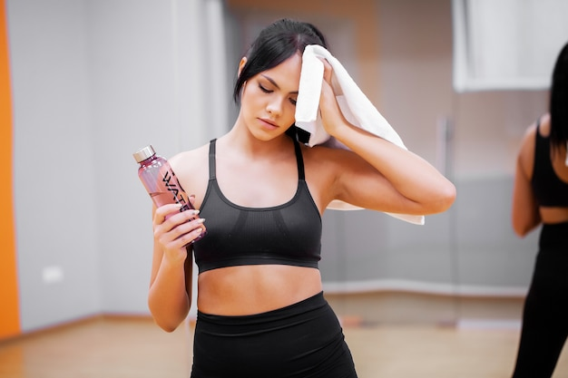 Mujer joven, bebida, agua limpia, en, gimnasio de la aptitud Foto Premium