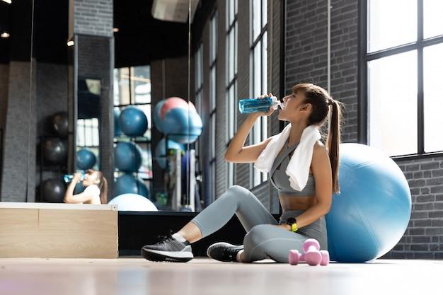 Mujer joven bebida asiática agua después de entrenamiento en una habitación Foto Premium