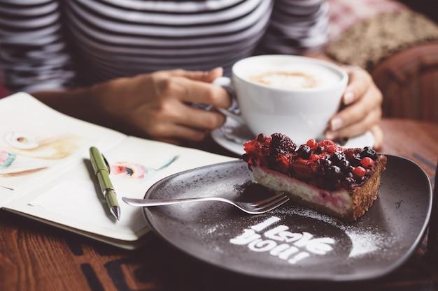 Mujer joven bebiendo café en café urbano Foto gratis
