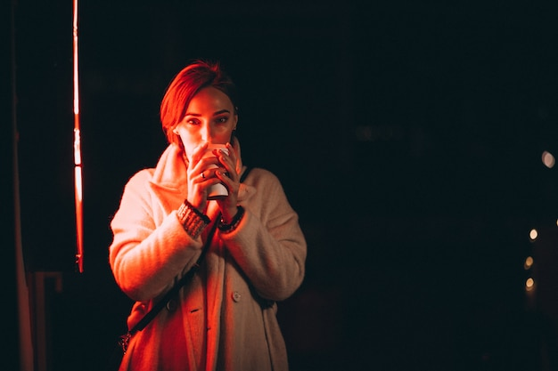 Mujer joven bebiendo café en la calle de noche Foto gratis