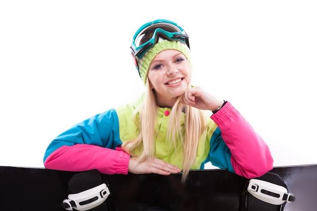 Mujer joven belleza en traje de esquí y gafas de esquí sentarse con sbowboard Foto Premium