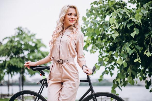 Mujer joven en una bicicleta en el parque Foto gratis