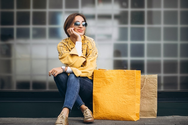 Mujer joven con bolsas de compras en la ciudad Foto gratis