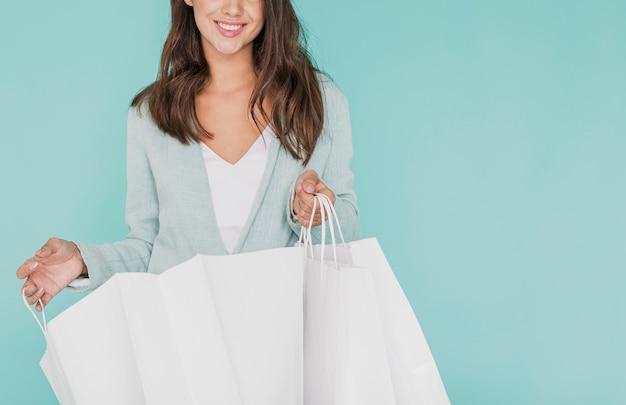 Mujer joven con bolsas de compras sobre fondo azul Foto gratis