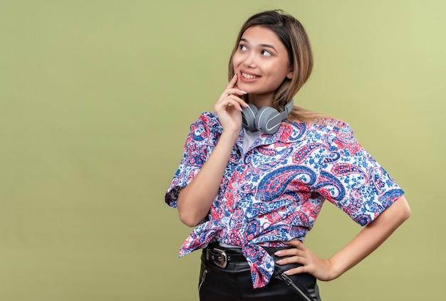 Una mujer joven y bonita en camisa estampada de paisley
