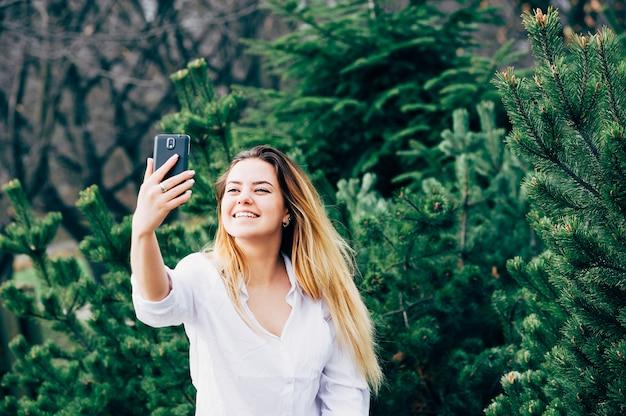 Una mujer joven y bonita sonriendo y haciendo selfie en un parque Foto Premium