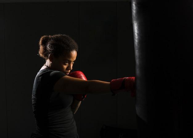 Mujer joven boxeando en el gimnasio Foto gratis