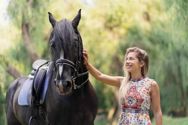 Mujer joven con un caballo Foto gratis