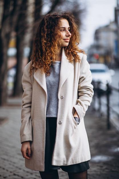 Mujer joven con cabello rizado fuera de la calle Foto gratis