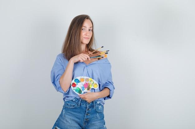 Mujer Joven Con Camisa Azul Pantalones Cortos Sosteniendo Herramientas De Pintura Y Mirando Orgulloso Foto Gratis