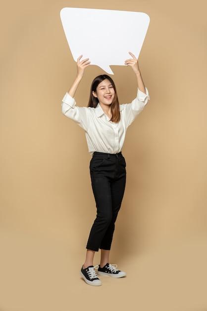 Una mujer joven con una camisa blanca sosteniendo un símbolo de cuadro de pensamiento Foto gratis