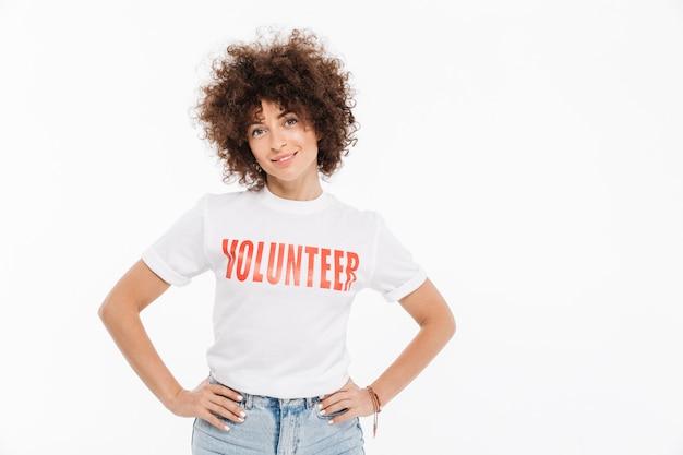 Mujer joven en camisa voluntaria de pie con las manos en las caderas Foto gratis