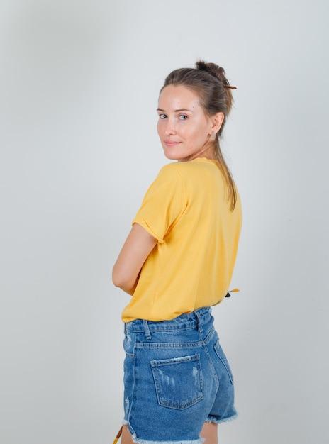 Mujer Joven En Camiseta Amarilla Pantalones Cortos De Jeans Mirando A Camara Con Herramientas De Pintura Foto Gratis