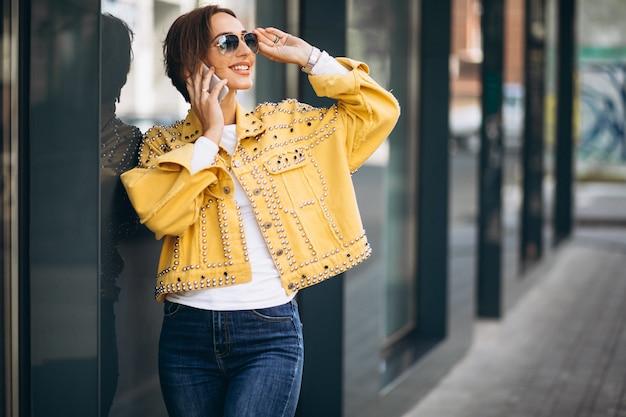 Mujer joven en chaqueta amarilla con teléfono afuera en la calle Foto gratis