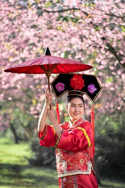 34eb60477 Mujer joven china hermosa que lleva el cheongsam tradicional rojo en ...
