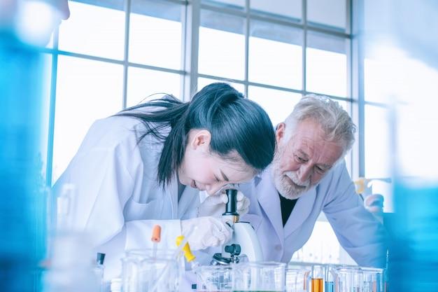 Mujer joven científico y médico con microscopio en laboratorio Foto Premium
