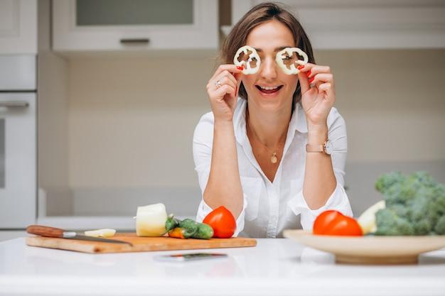 Mujer joven en la cocina preparando el desayuno Foto gratis