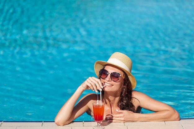 Mujer joven con un cóctel sentado en una piscina Foto gratis